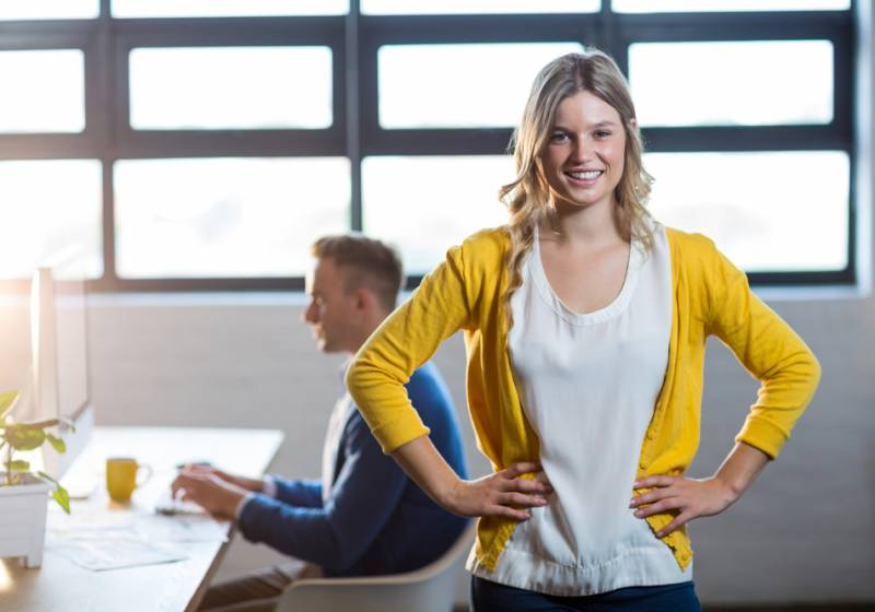 Portrait of happy woman by colleague in office